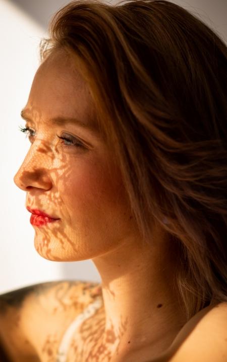 DVO Fotografie - Boudoir highkey vrouw kijkend uit raam met schaduw patroon in haar gezicht