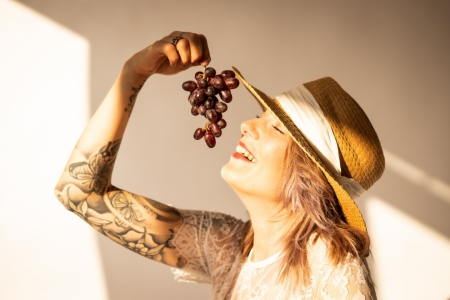 DVO Fotografie - Boudoir highkey vrouw lachend met een tros druiven in haar hand boven haar mond
