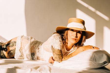 DVO Fotografie - Boudoir highkey vrouw liggend op bed met kussen onder haar hoofd en hoed op zwoel kijkend in de camera