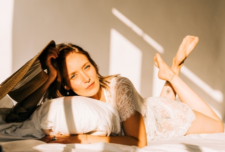 DVO Fotografie - Boudoir highkey vrouw liggend op bed met kussen onder haar hoofd kijkend in de camera