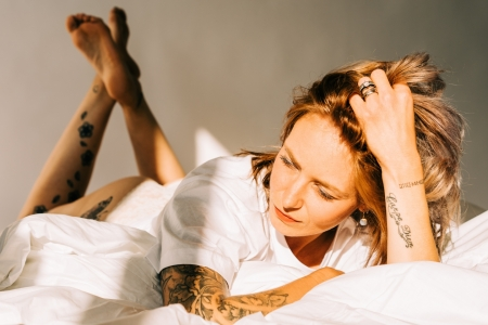 DVO Fotografie - Boudoir highkey vrouw liggend op bed met kussen onder haar hoofd wegkijkend van de camera