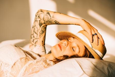 DVO Fotografie - Boudoir highkey vrouw liggend op haar rug met hoed op haar hoofd genietend van de zon