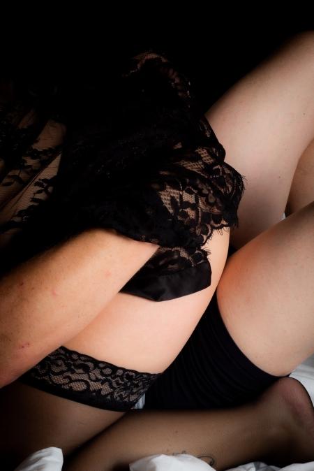 DVO Fotografie - Boudoir koppel vrouw zit om man die zijn handen onder haar kleding heeft