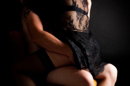 DVO Fotografie - Boudoir koppel vrouw zit op schoot van man en man heeft zijn hand op haar billen
