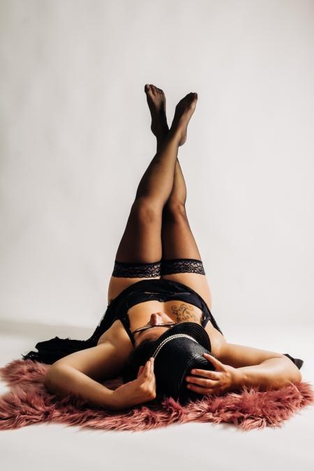 DVO Fotografie - Boudoir vrouw liggend op haar rug met benen omhoog en hoedje op