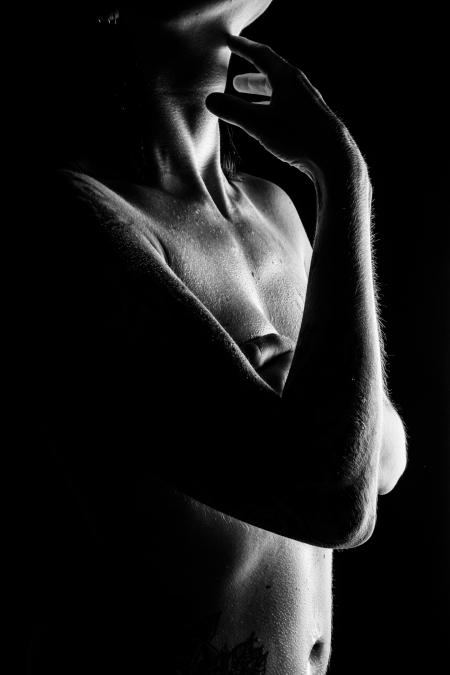 DVO Fotografie - boudoir lowkey vrouw met arm op haar borsten en hand op haar nek in rimlicht