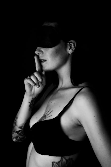 DVO Fotografie - Boudoir lowkey vrouw met blinddoek op en vinger voor haar moet fluisteren