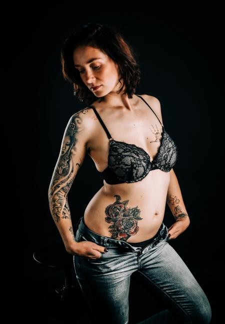 DVO Fotografie - Boudoir tattoo vrouw in lingerie met haar handen in haar zakken schuin kijken naar beneden