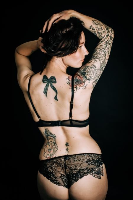 DVO Fotografie - Boudoir tattoo vrouw met haar rug naar de camera met handen op haar hoofd