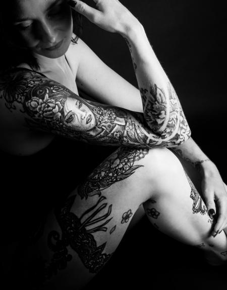 DVO Fotografie - Boudoir tattoo vrouw naar beneden kijken in rimlicht