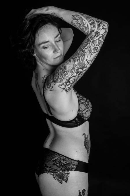 DVO Fotografie - Boudoir tattoo vrouw schuin naar de camera gedraaid met haar handen op het hoofd