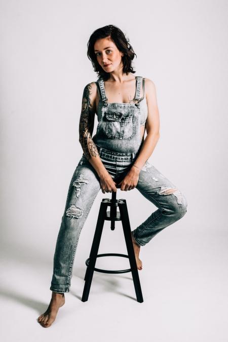 DVO Fotografie - Boudoir tattoo vrouw zit op kruk in tuinpak kijkend in de camera