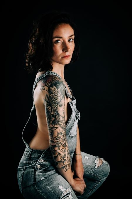 DVO Fotografie - Boudoir tattoo vrouw zit op kruk in tuinpak zwoel kijkend in de camera