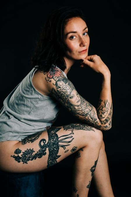 DVO Fotografie - Boudoir tattoo vrouw zit op poef schuin zittend en kijken naar de camera steunend met een arm op haar knie en hand onder haar kin