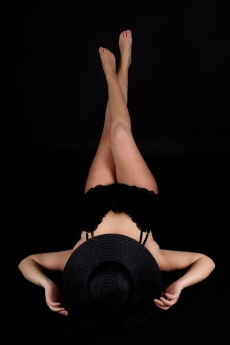 DVO Fotografie - Boudoir lowkey vrouw liggend op haar rug met benen gekruist omhoog met haar handen aan haar hoed