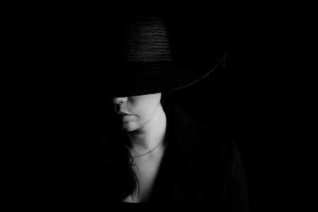 DVO Fotografie - Boudoir lowkey vrouw met zwarte hoed half over haar gezicht zwart wit