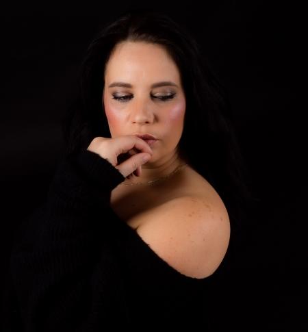 DVO Fotografie - Boudoir lowkey vrouw naar beneden kijkend met hand voor haar mond